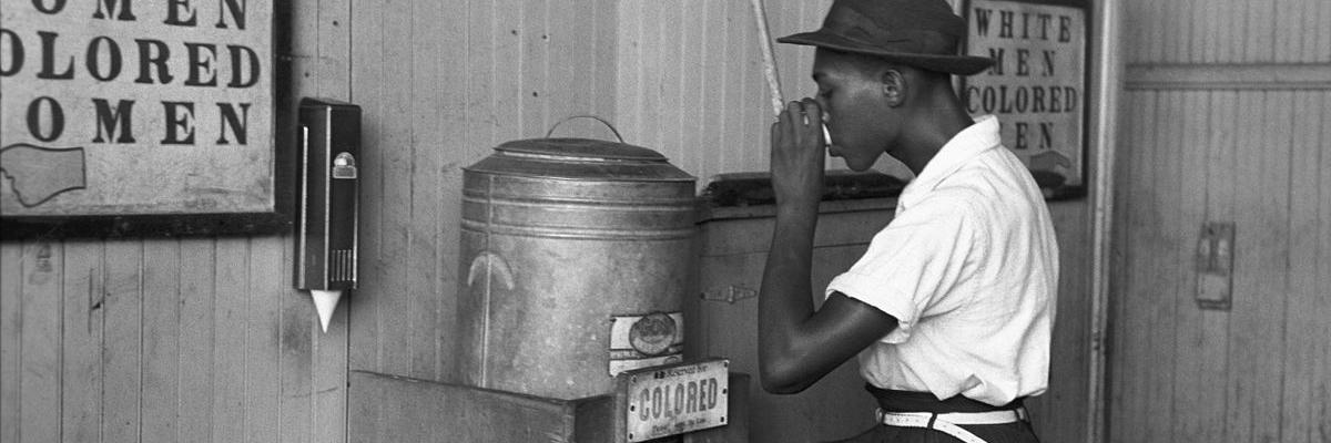 """Colored"" drinking fountain from mid-20th century with african-american drinking (Original caption: ""Negro drinking at ""Colored"" water cooler in streetcar terminal, Oklahoma City, Oklahoma""). Source [wikimedia commons]"