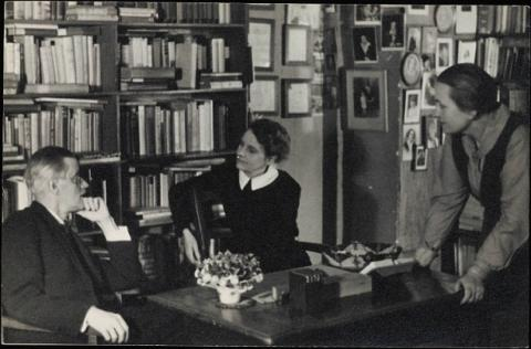 James Joyce photographed with Sylvia Beach and Adrienne Monnier at Shakespeare and Company in Paris in c. 1920. Source [wikimedia commons]